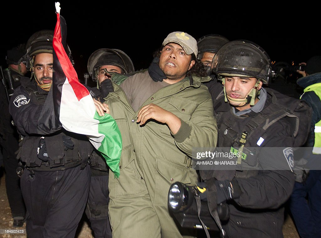 Israeli border policemen evacuate a Palestinian protester as they dismantle a protest camp in the controversial West Bank area known as E1 located east of Jerusalem and near the Jewish settlement of Maaleh Adumim early on March 24, 2013. Hundreds of Israeli police dismantled the protest camp on the outskirts of Jerusalem overnight, activists and police said. Activists set up the camp, which they dubbed Bab al-Shams or 'Gate of the Sun' in Arabic, in a bid to draw attention to Israeli plans to boost settlement building in the area known as E1.