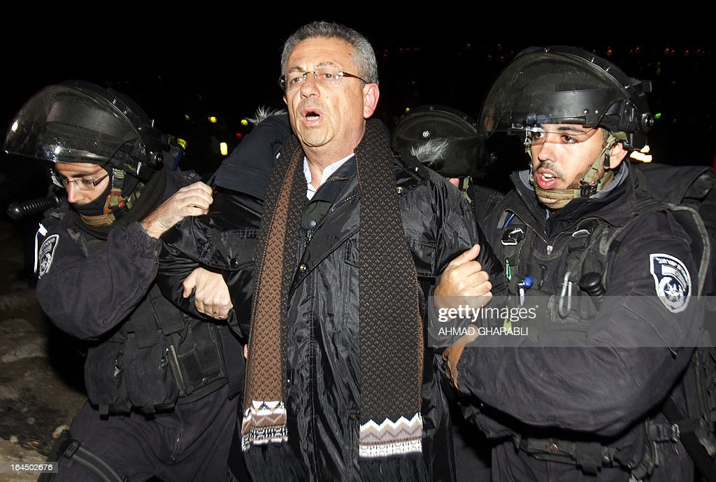Israeli border policemen evacuate Palestinian legislator Mustafa Barghouti (C) from a protest camp in the controversial West Bank area known as E1 located east of Jerusalem and near the Jewish settlement of Maaleh Adumim early on March 24, 2013. Hundreds of Israeli police dismantled the protest camp on the outskirts of Jerusalem overnight, activists and police said. Activists set up the camp, which they dubbed Bab al-Shams or 'Gate of the Sun' in Arabic, in a bid to draw attention to Israeli plans to boost settlement building in the area known as E1.