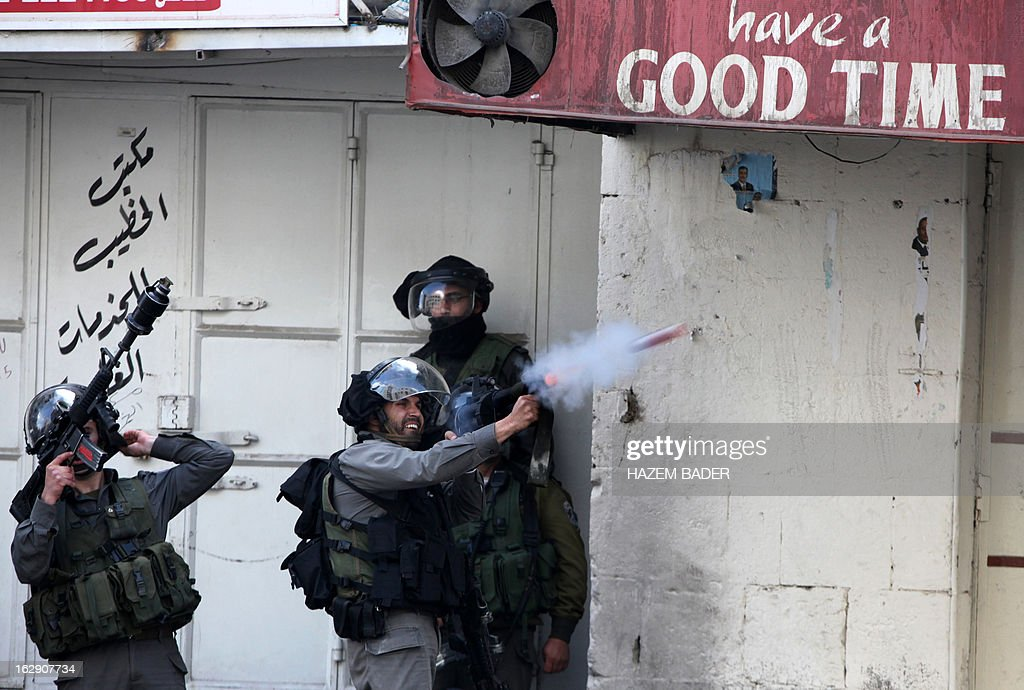 Israeli border policemen fire tear gas towards Palestinian protesters during clashes in the old city of Hebron on March 1, 2013 following a protest demanding the reopening of Shuhada Street, the one-time heart of the city. Flanked by a handful of Jewish settlement enclaves, the Shuhada Street was partially closed off in 1994 after local settler Baruch Goldstein opened fire on Muslim worshippers at the city's Al-Ibrahimi mosque, killing 29 of them.