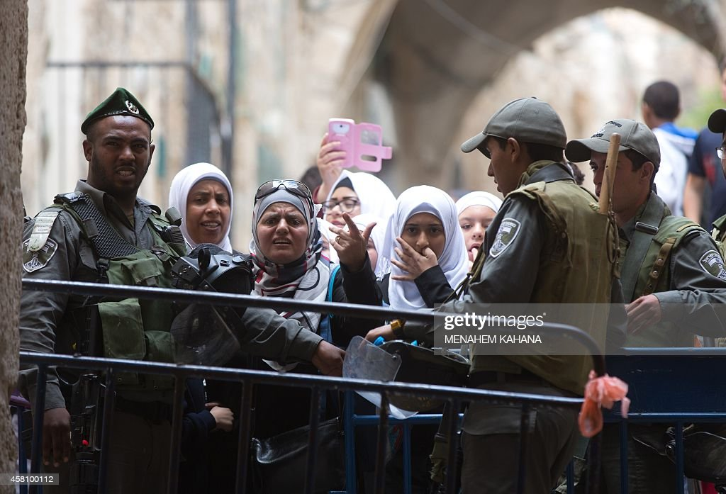 Israeli border policemen prevent Palestinian woman from entering the AlAqsa mosque compound in the old city of Jerusalem on October 30 2014 after...
