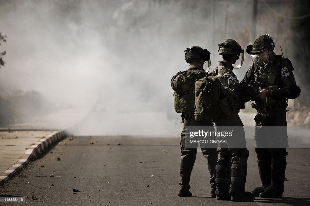 Israeli border policemen stand amid a cloud of tear gas during clashes with Palestinian stone throwers following the funeral of Mohammad Asfour in the West Bank village of Abud on March 8, 2013. Asfour died of his wounds on March 7, after he was hit by a rubber-coated steel bullet during a demonstration over the death of a Palestinian prisoner in Israeli custody in February. AFP PHOTO/MARCO LONGARI