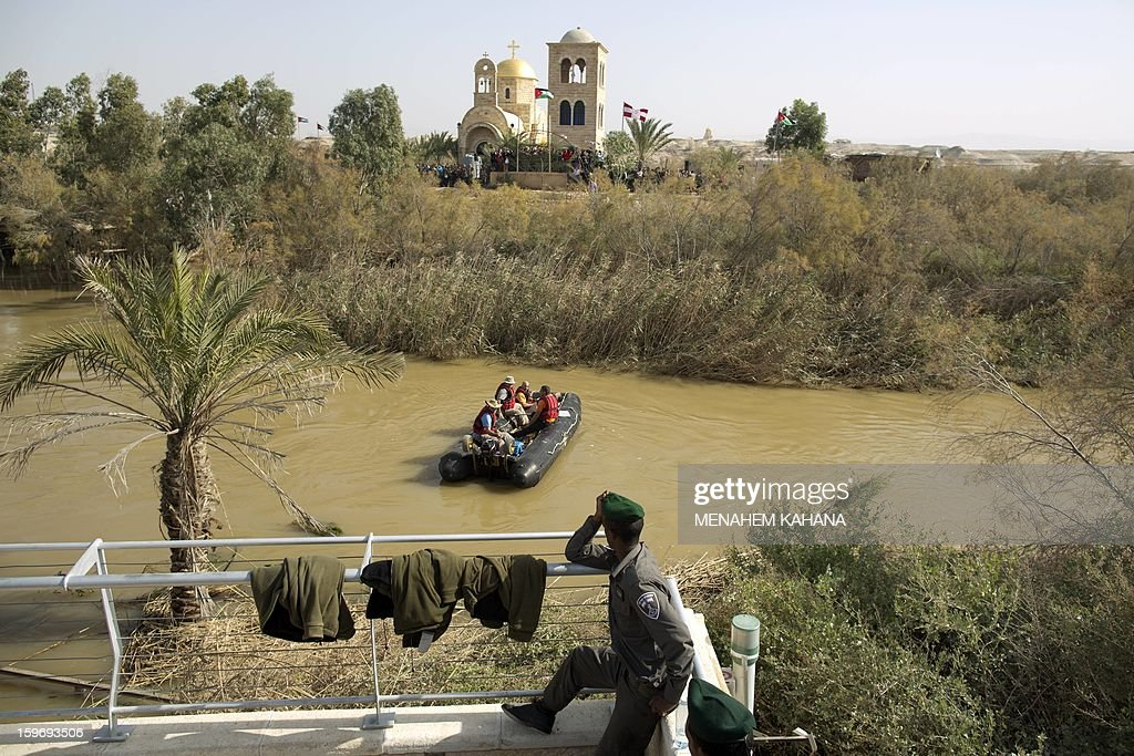 Israeli border policemen stand guard along the Jordan River during a ceremony as part of the Orthodox Feast of the Epiphany on January 18, 2013 at the Qasr al-Yahud baptismal site in the West Bank by the Jordan River. Greek Orthodox Patriarch of Jerusalem Theophilos III led a ceremony during which thousands of Orthodox Christians braved rain to plunge into plastic tubs filled with its murky water to celebrate Jesus's baptism.