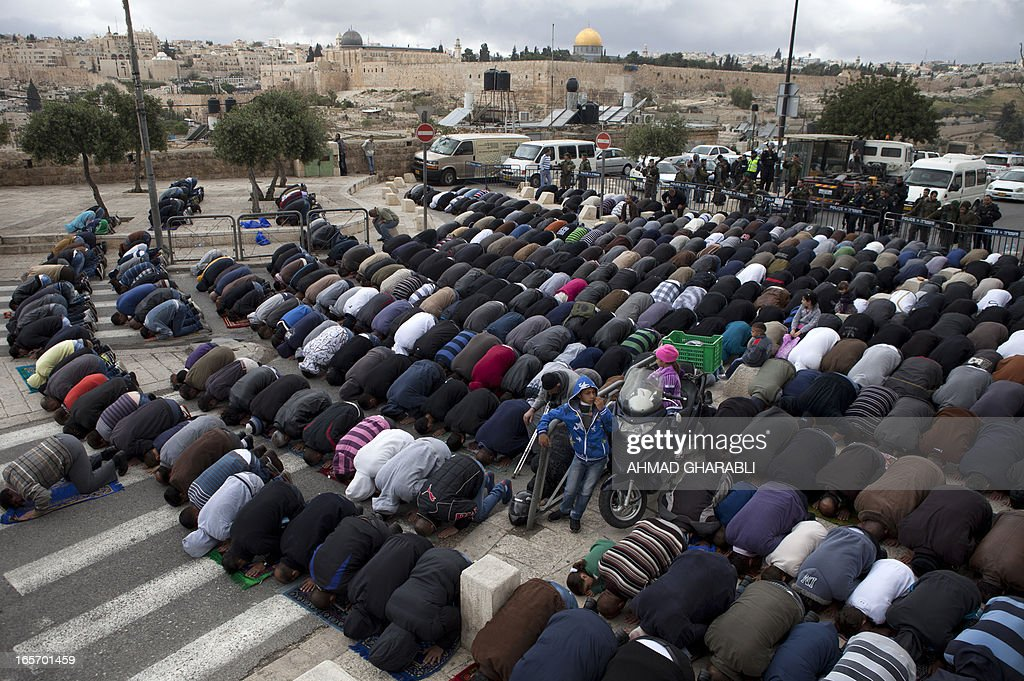 Israeli border policemen stand guard as a Palestinian Muslims perform Friday prayers on a street in the Arab east Jerusalem neighborhood of Ras-Al Amud with the al-Aqsa mosque in the background, on April 5, 2013. Israel's police deployed reinforcements in Jerusalem, fearing days of violent protests in the West Bank could spread to the flashpoint Al-Aqsa mosque compound after weekly Muslim prayers.