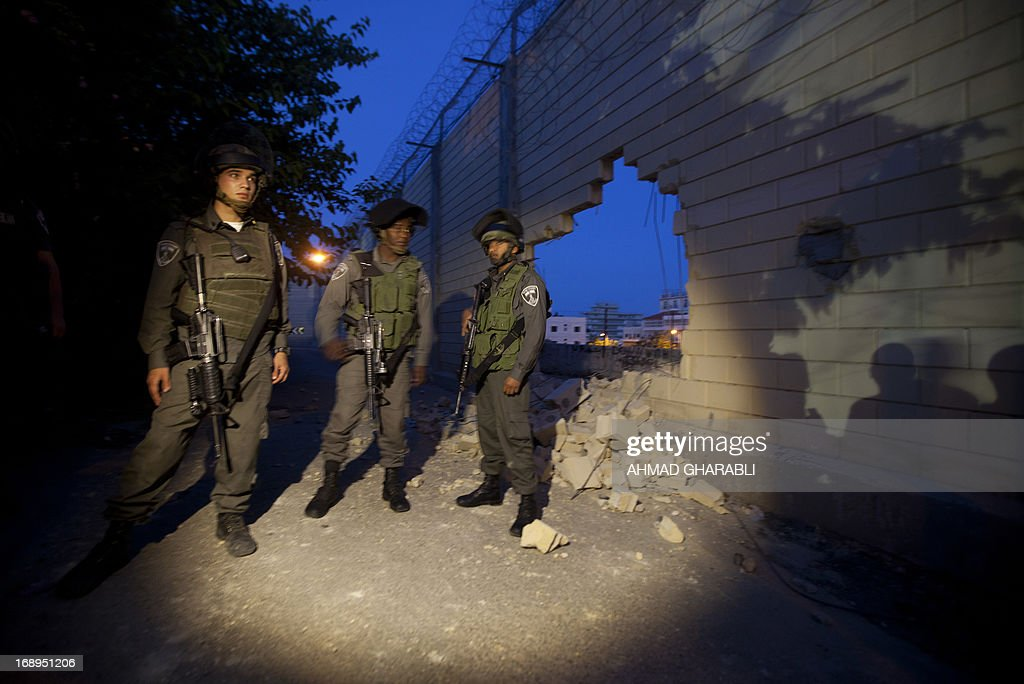 Israeli border policemen stand guard next to a destroyed section of Israel's controversial separation barrier in the West Bank village of Abu Dis on the outskirts of Jerusalem on May 17, 2013 after Palestinian protesters broke through it. Israel says the barrier is needed to prevent attacks but Palestinians, who refer to it as an 'Apartheid Wall,' say it cuts them off from occupied land that should be part of their future state. The International Court of Justice (ICJ) issued a non-binding resolution in 2004 calling for those parts of the barrier inside the West Bank to be torn down and for further construction in the territory to cease. Israel has ignored the ICJ ruling.