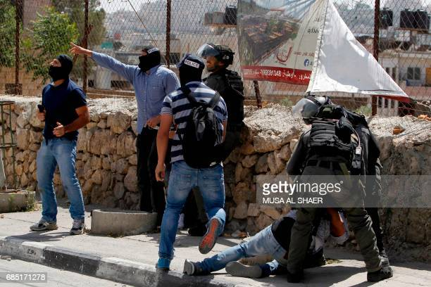 Israeli borderguards and undercover police detain a Palestinian protester during clashes at the entrance of the West Bank city of Bethlehem on May 19...