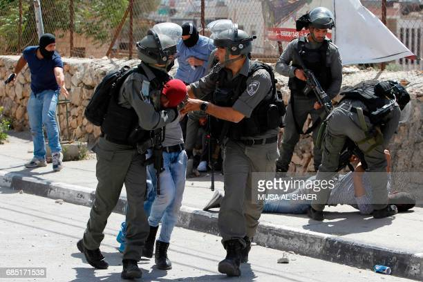TOPSHOT Israeli borderguards and undercover police detain a Palestinian protester during clashes at the entrance of the West Bank city of Bethlehem...