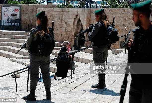 TOPSHOT Israeli borderguards stand guard as Palestinian women walk outside Damascus Gate in Jerusalem's Old City on June 18 2017 / AFP PHOTO / AHMAD...