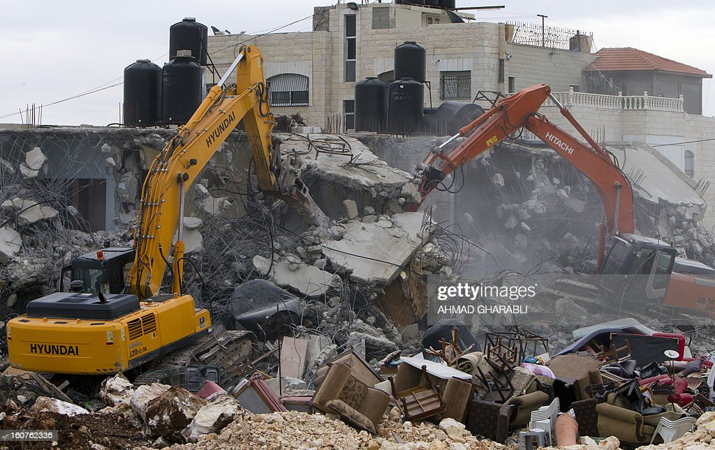 Israeli bulldozers destroys a Palestinian house in the Arab east Jerusalem neighborhood of Beit Hanina on February 5, 2013. Palestinian homes built without a construction permit are often demolished by order of the Jerusalem municipality. AFP PHOTO/AHMAD GHARABLI