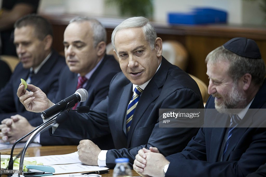 Israeli Cabinet Secretary Avichai Mandelblit (R) smiles while Israeli Prime Minister Benjamin Netanyahu holds a piece of apple as he welcomes the Jewish New Year during the weekly cabinet meeting in Jerusalem on September 1, 2013. The Israeli cabinet authorised on August 28 a partial call-up of army reservists amid growing expectations of a foreign military strike on neighbouring Syria, army radio reported.