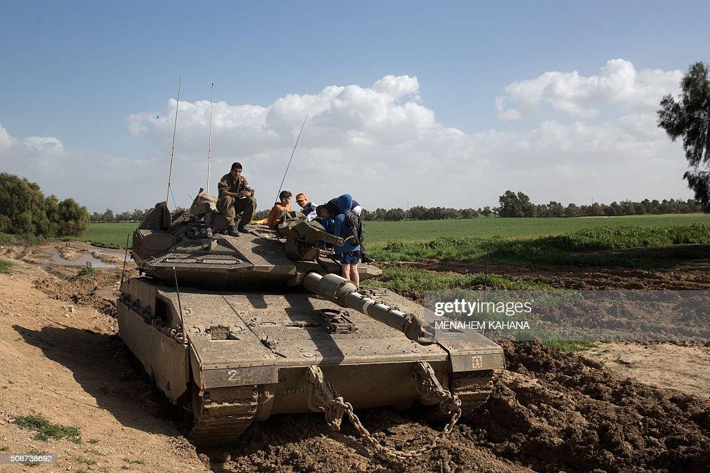 Israeli children from the nearby Kibbutz Nirim climb on an on-duty Merkava tank guarded by an Israeli soldier, as they enjoy a sunny day near the southern Israeli border with the Gaza Strip on February 6, 2016. / AFP / MENAHEM KAHANA