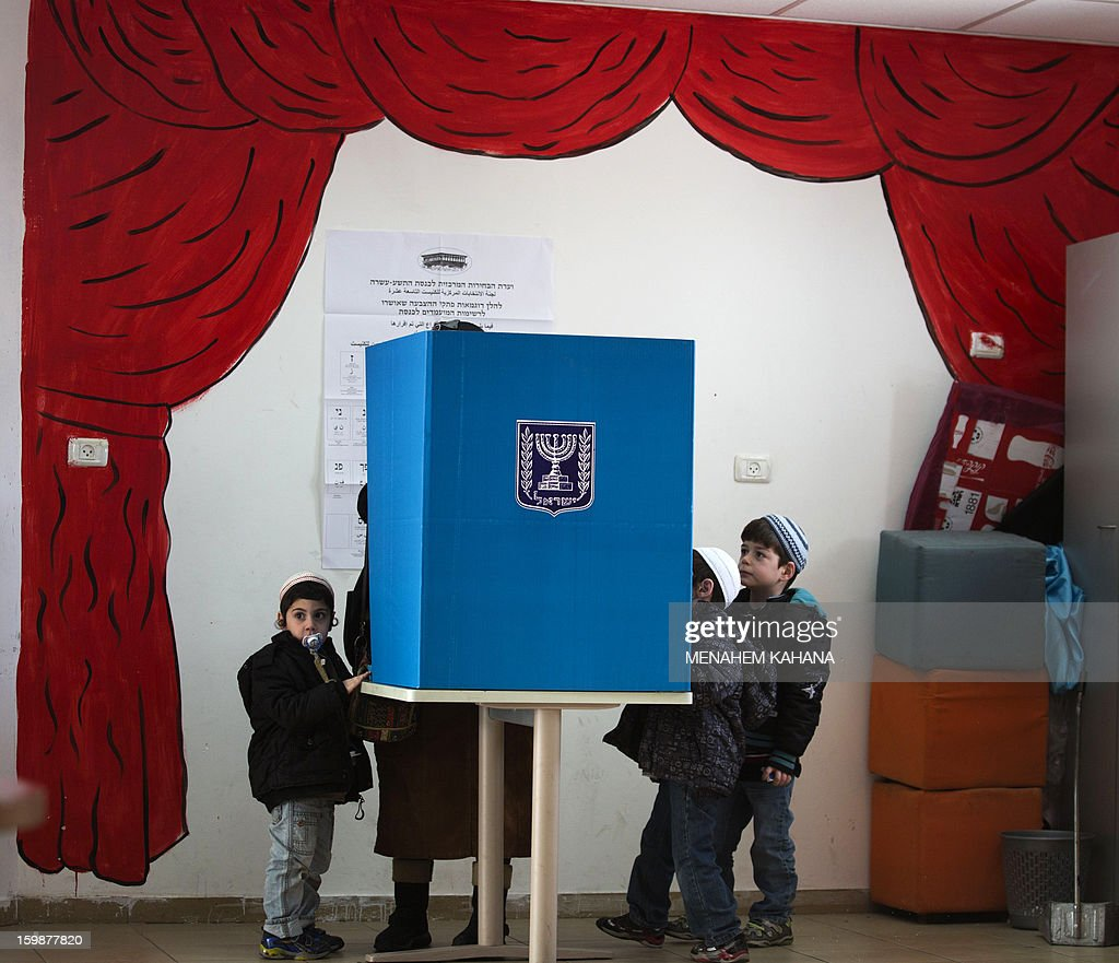 Israeli children gather around a voting booth as their mother marks her ballot at a polling station in the Jewish settlement of Har Homa in east Jerusalem on January 22, 2013. Voters across Israel and in settlements peppering the occupied West Bank cast ballots for the Israeli general election at more than 10,000 polling stations, with turnout standing at 38.3 percent after seven hours of voting. AFP PHOTO/MENAHEM KAHANA