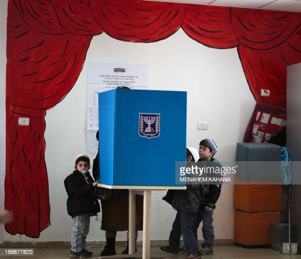 Israeli children gather around a voting booth as their mother marks her ballot at a polling station in the Jewish settlement of Har Homa in east...