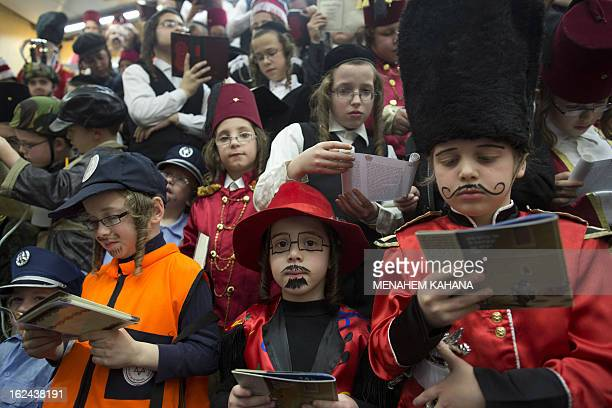 Israeli children in Purim costumes read the Esther scrolls at a synagogue in the Israeli town of Bnei Brak near Tel Aviv on February 23 2013 The...