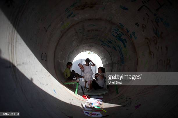 Israeli children play in a large concrete pipe used as a bomb shelter on November 19 2012 in Nitzan Israel According to reports November 19 at least...