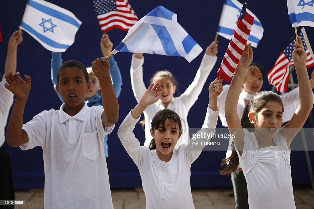 Israeli children wave Israeli and US flags as they sing during a rehearsal at the residence of President Shimon Peres in Jerusalem on March 19, 2013, a day ahead of US President Barack Obama's visit. Jerusalem was decked out with US flags and bunting as the Holy City geared up to roll out the red carpet for Wednesday's historic visit by US President Barack Obama.