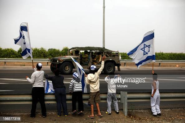 Israeli children wave their national flag as they greet an army convoy passing on a road leading to the IsraelGaza border near the southern Israeli...