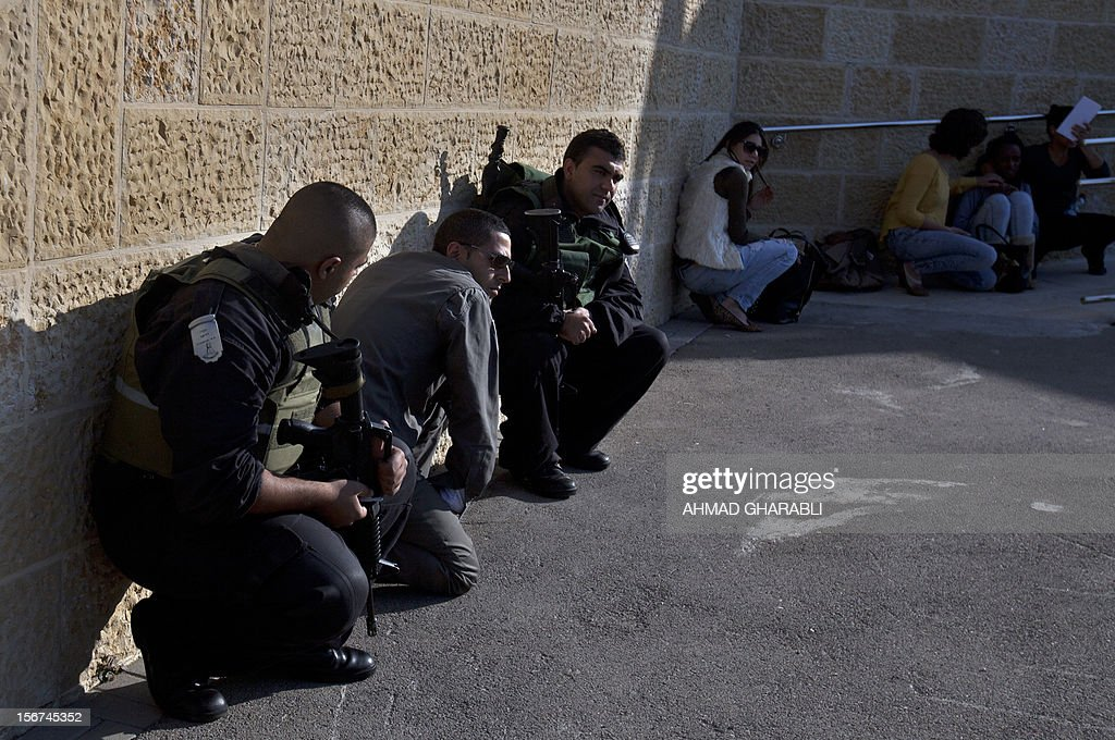 Israeli civilians and security forces take cover as air raid sirens sound around Jerusalem on November 20, 2012. A rocket struck just south of Jerusalem as UN chief Ban Ki-moon was to arrive for talks on ending the Gaza crisis, AFP correspondents said. AFP PHOTO/AHMAD GHARABLI