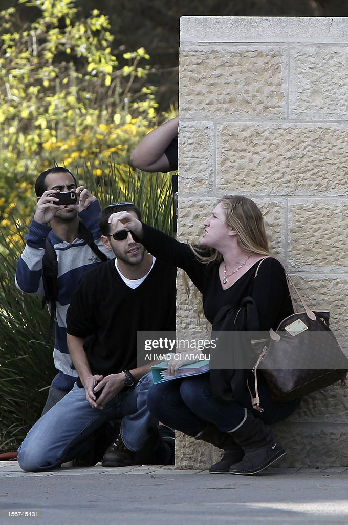 Israeli civilians find shelter behind a wall while a man takes pictures as air raid sirens sound around Jerusalem on November 20, 2012. A rocket struck just south of Jerusalem as UN chief Ban Ki-moon was to arrive for talks on ending the Gaza crisis, AFP correspondents said.