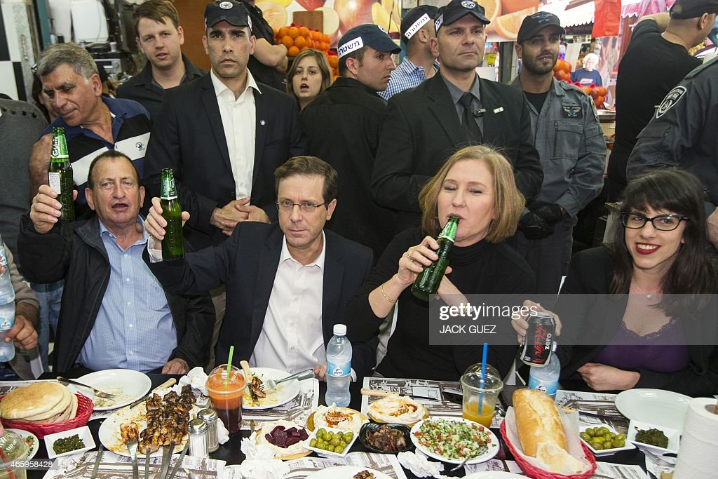 Israeli co-leaders of the Zionist Union list for the upcoming general election, Labour Party leader, Isaac Herzog (2ndL) and MP <a gi-track='captionPersonalityLinkClicked' href=/galleries/search?phrase=Tzipi+Livni&family=editorial&specificpeople=537394 ng-click='$event.stopPropagation()'>Tzipi Livni</a> (2ndR) have lunch at the outdoor Carmel Market on March 12, 2015 in the coastal Israeli city of Tel Aviv during their campaign. Israelis vote on March 17, 2015 in an election seen as a referendum on the tenure of Prime Minister Benjamin Netanyahu, who could lose but still secure a new term in power. AFP PHOTO / JACK GUEZ