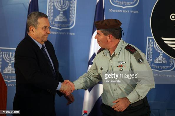 Israeli Defence Minister Ehud Barak shake hands with outgoing Chief of Staff Gabi Ashkenazi during a special ceremony at the Prime Minister's Office...