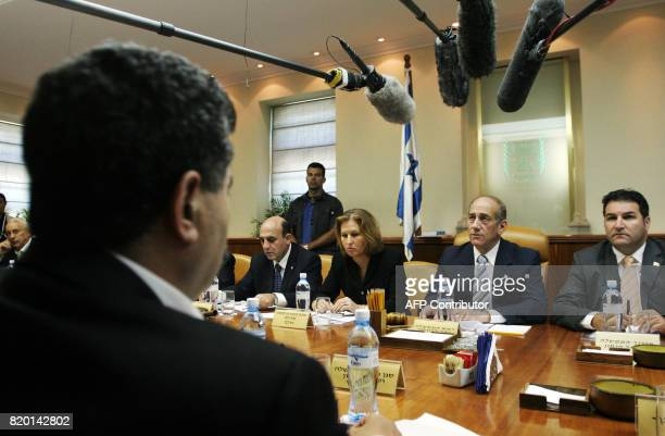 Israeli Defense Minister Amir Peretz watches as Israeli Prime Minister Ehud Olmert makes a statement as he chairs the weekly cabinet meeting in his...