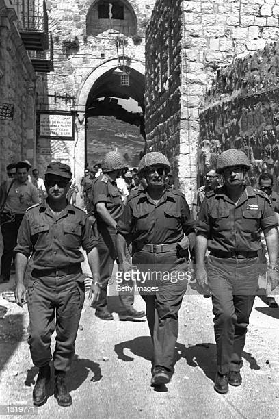 Israeli Defense Minister Moshe Dayan center flanked by army Chief of Staff Yitzhak Rabin right and General Uzi Narkiss enter the Old City through the...