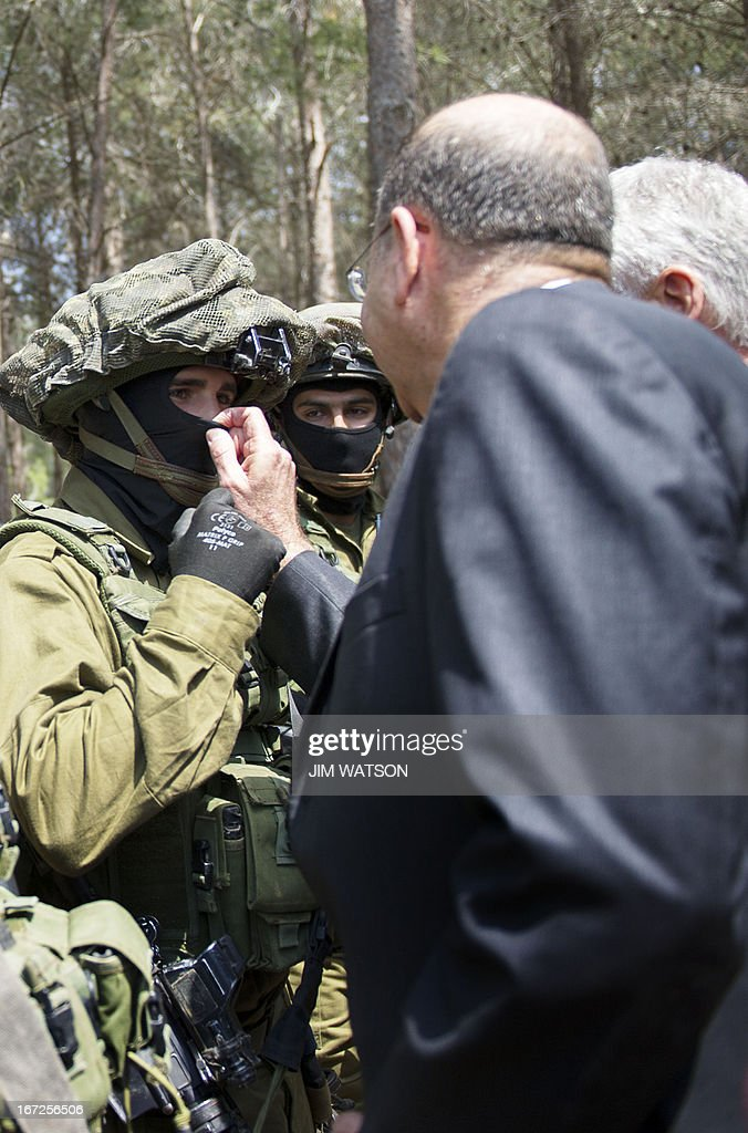Israeli Defense Minister Moshe Yaalon tries to uncover the face of a special forces member as US Secretary of Defense Chuck Hagel (R) visits a military K-9 unit training site at an army base near Tel Aviv, on April 23, 2013. Defence Secretary Chuck Hagel met Israel's Benjamin Netanyahu at the end of a three-day trip which saw him touting strong backing for Israel despite differences over Iran's nuclear project.