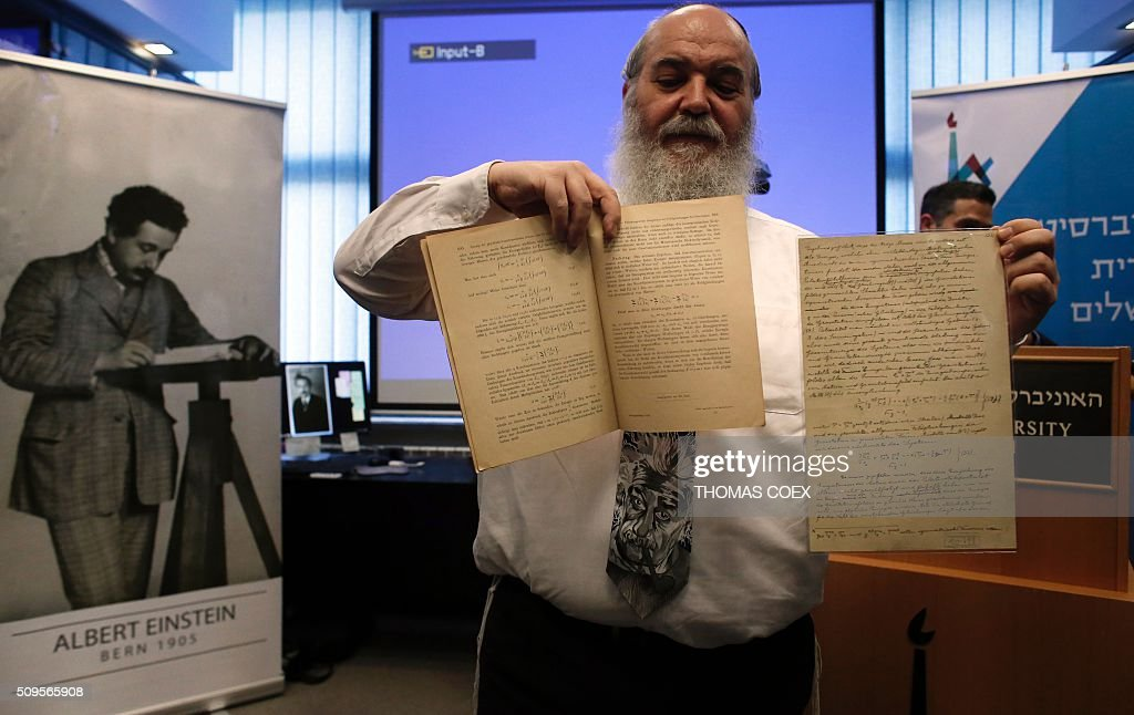 Israeli Doctor Roni Grosz, head of The Albert Einstein Archives at the Hebrew University of Jerusalem, shows the original document (R) written by Albert Einstein related to Albert Einstein's prediction of the existence of gravitational waves, on February 11, 2016 in Jerusalem. The Einstein theory was developed by Einstein 100 years ago, but had never been proved. One document is the first in which Einstein ever presented his theory of gravitational waves, the other is a page from the 46-page Theory of Relativity. / AFP / THOMAS COEX