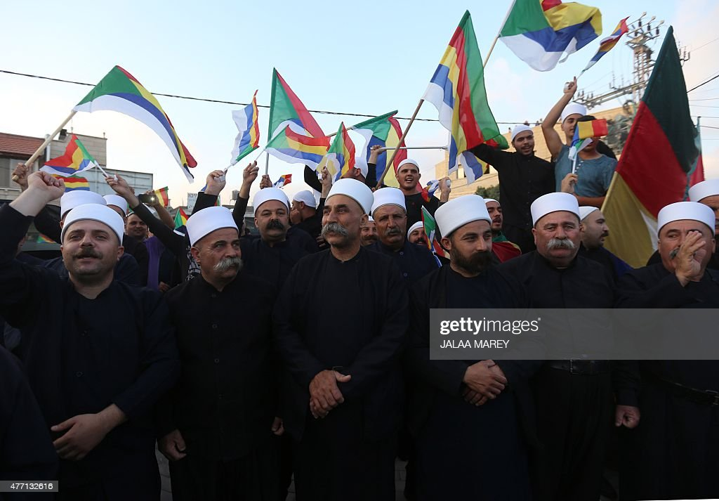 Israeli Druzes wave their community's flags during a demonstration in reaction to a shootout in northwest Idlib province in Syria that killed members...