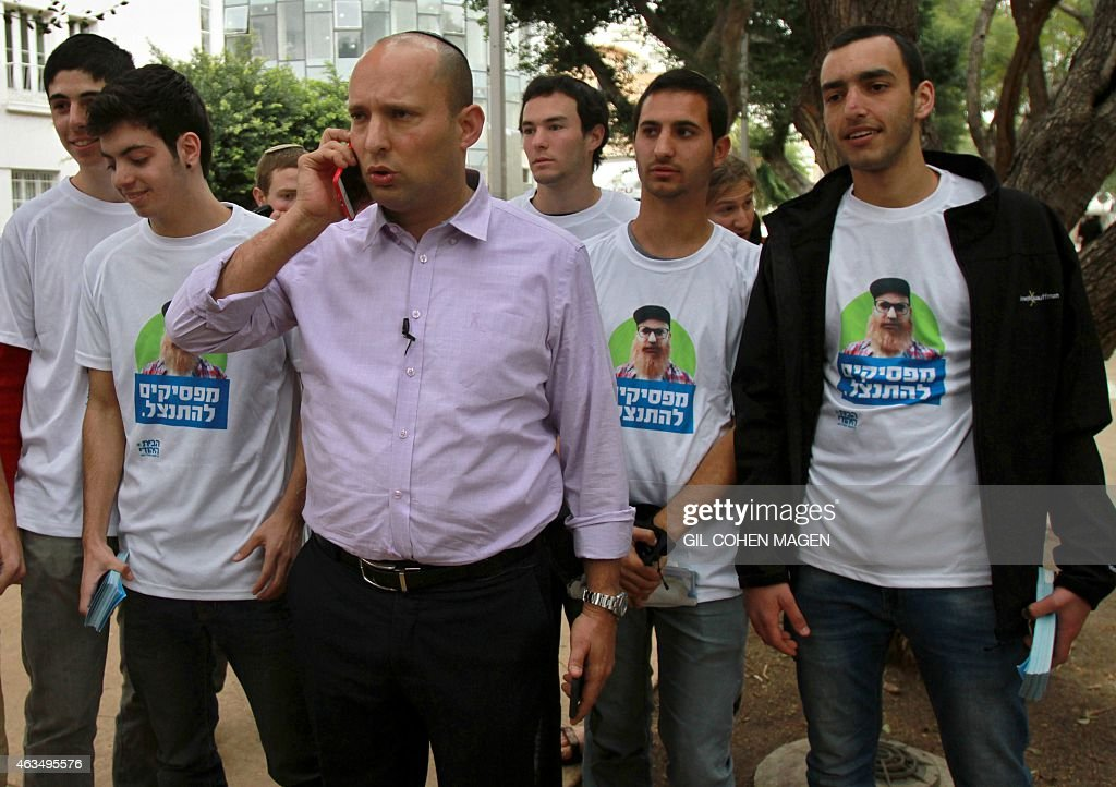 Israeli Economy Minister and head of the far-right Jewish Home party Naftali Bennett (C) speaks on the phone as he meets citizens in the streets of the coastal Israeli city of Tel Aviv on February 15, 2015 as part of his campaign ahead of the March 17 general elections. Recent polls have shown a tight race between Prime Minister Benjamin Netanyahu's right-wing Likud party and the Zionist Union but many voters remain undecided. AFP PHOTO / GIL COHEN-MAGEN