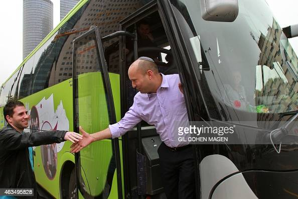 Israeli Economy Minister and head of the farright Jewish Home party Naftali Bennett shakes hands with a man as he meets citizens in the streets of...