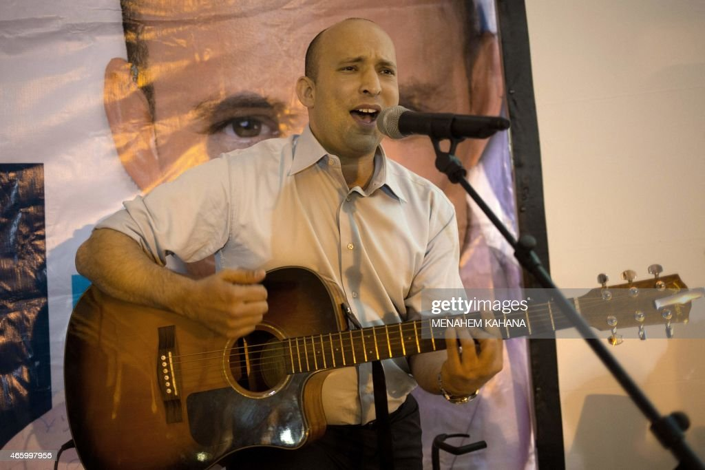 Israeli Economy Minister and head of the right-wing Jewish Home party, Naftali Bennett plays the guitar and sings during an election campaign gathering for the Jewish community in Kibbutz Kfar Etzion in the Gush Etzion settlement block in the West Bank, on March 12, 2015, ahead of a snap general election scheduled March 17. Bennett, 42, is a champion of the settler movement and a key challenger of Netanyahu to head Israel's rightwing.