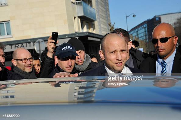 Israeli Economy Minister Naftali Bennett pays his respects at the Hyper Cacher prior to a mass unity rally to be held in Paris following the recent...