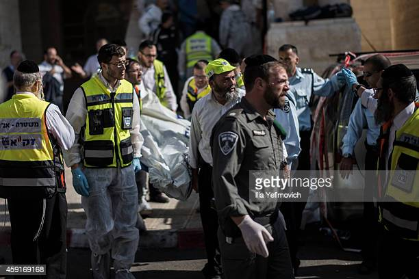 Israeli emergency personnel take out a body of an Israeli man outside a synagogue on November 18 2014 in Jerusalem Israel Four Israelis have been...