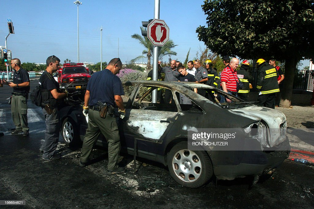 OUT == Israeli emergency services and policemen inspect a car that was hit by rocket shrapnel, fired from Gaza, in the city of Holon, near Tel Aviv, on November 18, 2012. Sirens sounded across Tel Aviv for a fourth straight day, AFP correspondents said, as Israeli police confirmed two rockets had been intercepted over the city by the Iron Dome defence system, designed to intercept and destroy incoming short-range rockets and artillery shells. AFP PHOTO / RONI SCHUTZER