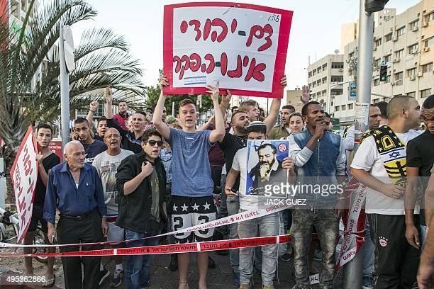 Israeli farright demonstators hold a placard that reads in Hebrew 'The Jewish blood will not be abandoned' and a poster of late Brooklynborn Rabbi...