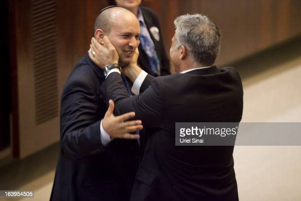 Israeli Finance Minister Yair Lapid and Minister of Economics and Trade Naftali Bennett embrace during a swearingin ceremony at the Knesset on March...