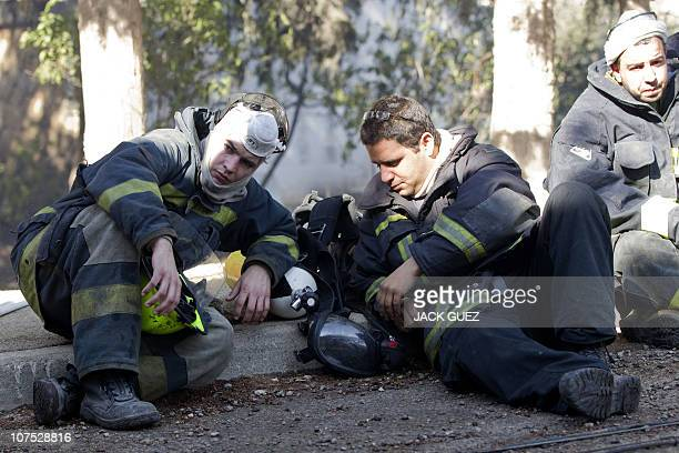 Israeli firefighters take a break after dousing flames in the village of Ein Hod on December 4 2010 as the massive fire ripping through northern...