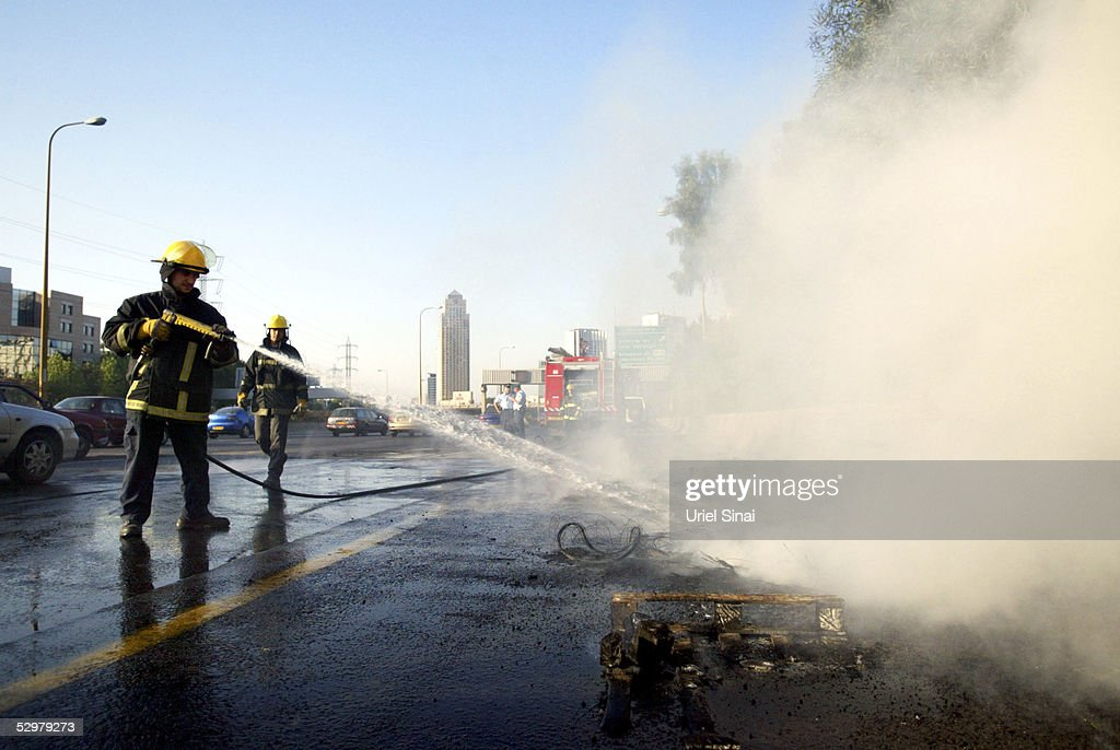 Israeli firemen spray water on burning tires set on fire on the highway between Tel Aviv and Jerusalem by Jewish settlers opposed to Prime Minister...