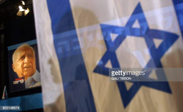 A Israeli flag is seen next to the poster of ailing prime minister Ariel Sharon early 29 March 2006 at the temporary Kadima meeting point set up...