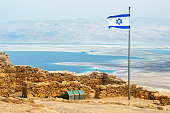 Aerial view on the Judaean Desert with the drying up Dead Sea from the Masada plateau with the waving flag of Israel and the ruins of the Herod palace on the foreground