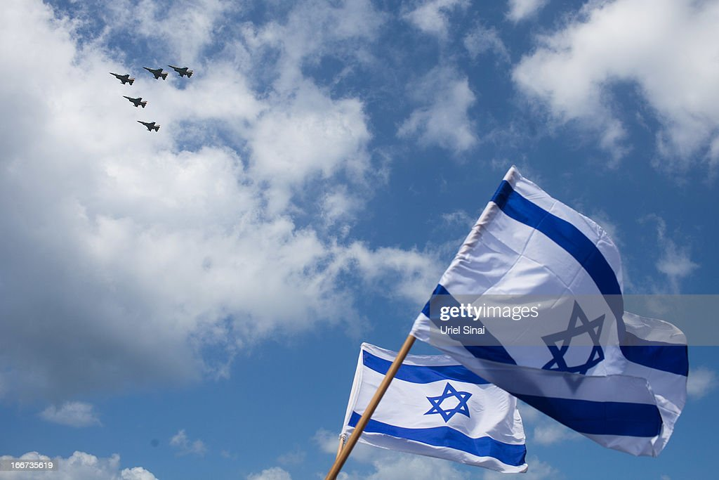 Israeli flags wave on the beach in the Mediterranean sea as a military air show marks the 65th anniversary of Israel's independence on April 16 2013...