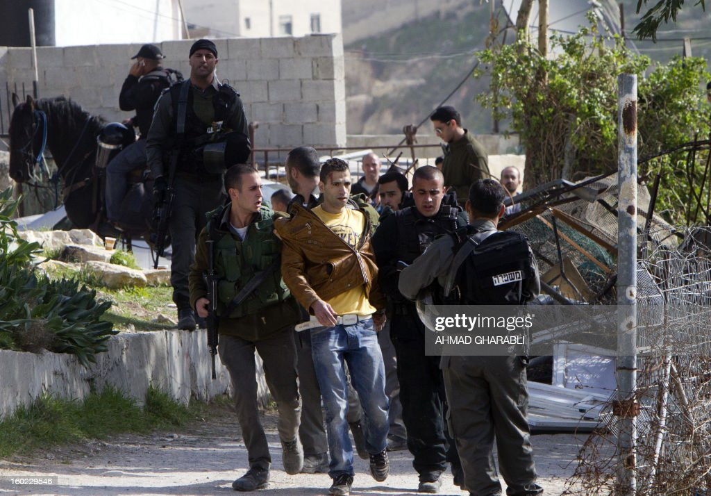 Israeli forces arrest a Palestinian man as clashes broke out while Israeli bulldozers demolished several structures in the east Jerusalem Arab neighbourhood of Silwan in Jerusalem's old city on January 28, 2013. Nine people were injured and seven arrested as residents of the buildings threw stones at Israeli forces.