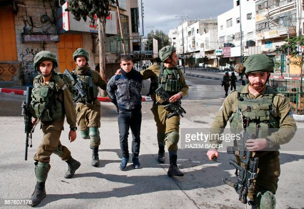 Israeli forces detain a Palestinian protester during clashes that followed protests against a decision by US President Donald Trump to recognise...