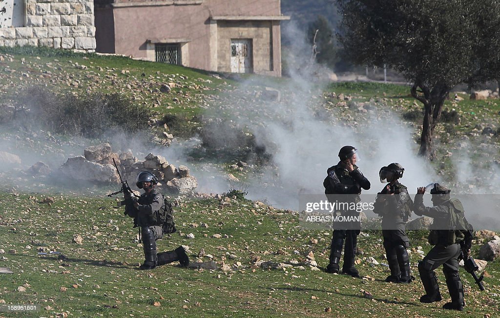 Israeli forces keep position during clashes with Palestinian protestors following a march organised by residents of the West Bank village Nabi Saleh to protest against the expansion of Jewish settlements on Palestinian land, on January 4, 2013 .