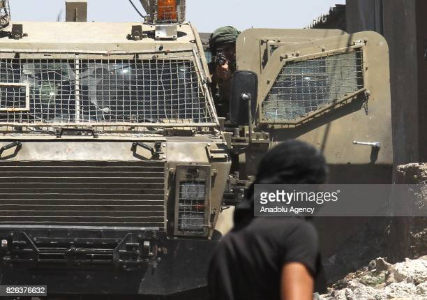 Israeli forces member points a gun as they intervene Palestinian demonstrators during clashes following a demonstration against the recent Israeli...