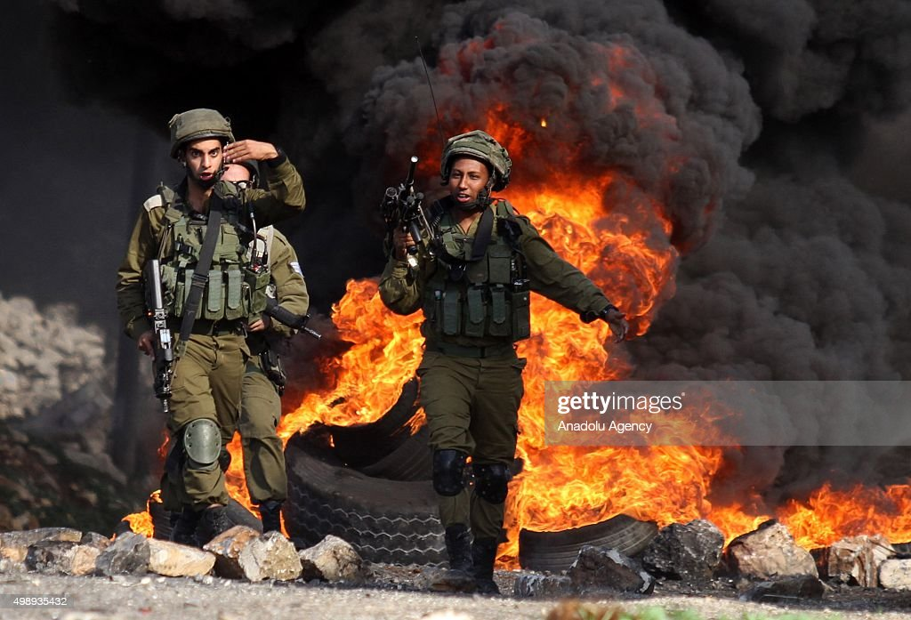 Israeli forces walk past burning tires during clashes between Palestinians and Israeli security forces in Kafr Kadum village of Nablus, West Bank on November 27, 2015.
