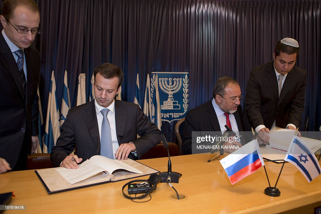 Israeli Foreign Ministedr Avigdor Lieberman (C-R) and Russian Deputy Prime Minister Arkady Vladimirovich Dvorkovich (C-L) sign two bilateral agreements on lowering cellphone roaming rates and on tourism cooperation between Israel and Russia on December 4 2012 in Jerusalem.