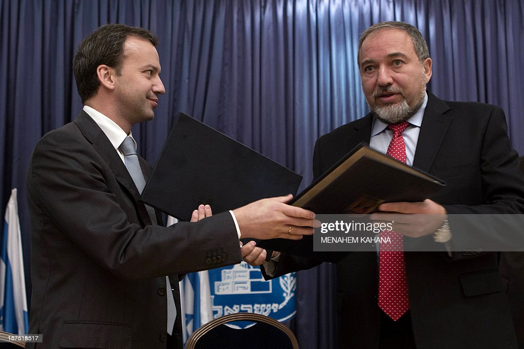 Israeli Foreign Ministedr Avigdor Lieberman (R) and Russian Deputy Prime Minister Arkady Vladimirovich Dvorkovich (L) exchange documents after signing two bilateral agreements on lowering cellphone roaming rates and on tourism cooperation between Israel and Russia on December 4 2012 in Jerusalem.