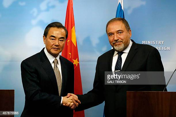 Israeli Foreign Minister Avigdor Lieberman shakes hand with his Chinese counterpart Wang Yi during a press conference on December 19 2013 at the...